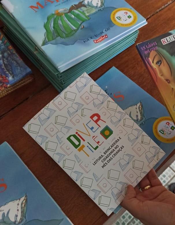 Uma pessoa segura a cartilha DivertiLê e uma caixa de lápis de cor. Ao fundo, estão livros de literatura infantil.
