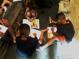 Foto de crianças brincando com livros de colorir.