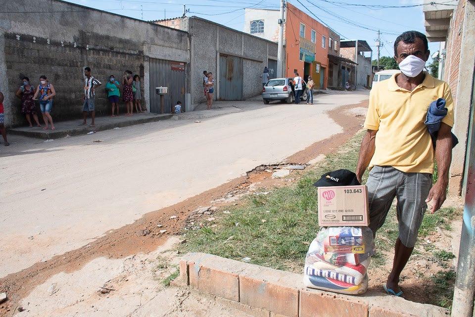 Um homem negro de máscara está de pé junto a uma cesta básica. Ele está em uma rua, onde vemos uma fila de pessoas para recolher doações