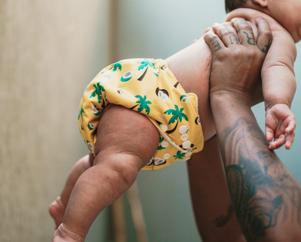 Bebê usando fralda ecológica amarela e estampada é suspenso pelas mãos de uma pessoa adulta.